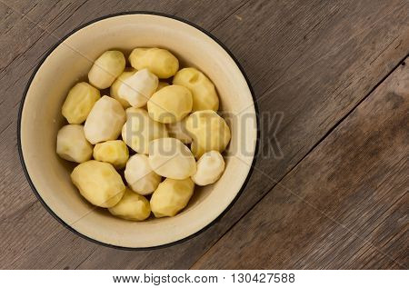 peeled raw potatoes in an enamel pot on the old boards. top view close-up