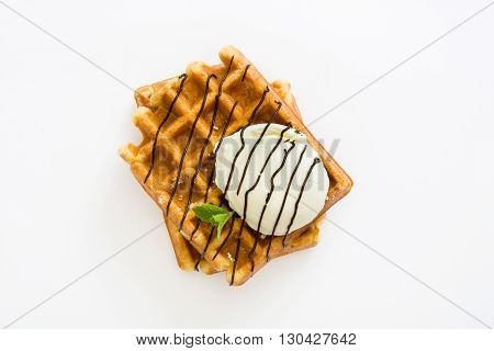 Waffles with chocolate sauce, ice cream and mint isolated