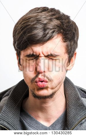 Grimacing man in pain against a white background