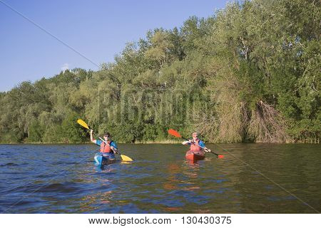 Two guys travel the river on a kayaking in the summer.