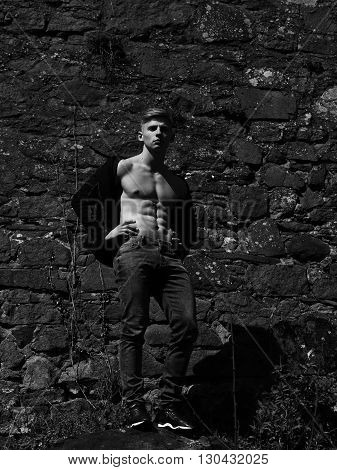 Sexy man athletic young with handsome face muscular body and bare torso pose in jeans outside black and white on mural background