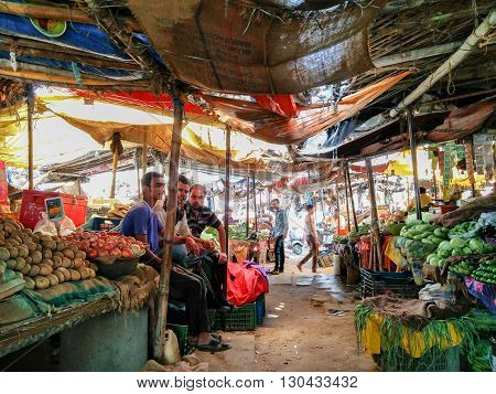Jaipur, India -13th May 2016 : traditional vegetable sellers sitting in a makeshift market of bamboo poles and sacks, selling vegetables from their farms.