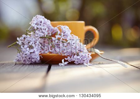 Orange cup with a spoon and a lilac inflorescence on a wooden table.