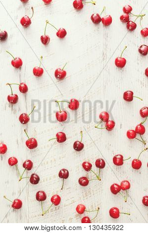 Cherry background. Red cherries scattered on rustic table. Overhead view, blank space