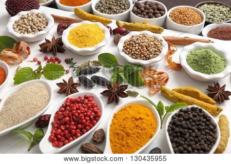 Colorful aromatic Indian spices and herbs on a wooden white background.