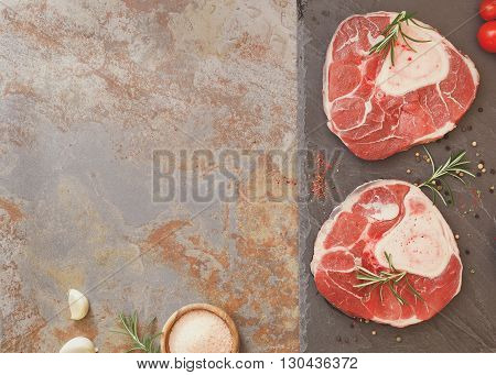 Raw veal shank. Raw fresh sliced veal shank and Ingredients for making Osso Buco on rustic background.  Overhead view, vintage toned image, blank space