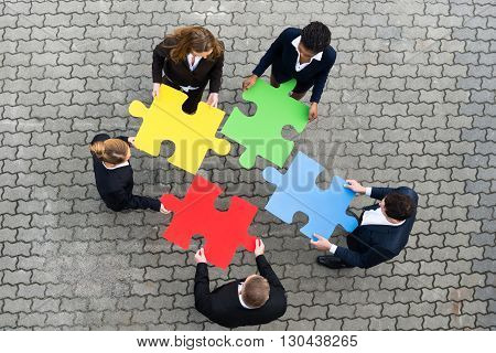 High Angle View Of Businesspeople Holding Colorful Puzzle Pieces