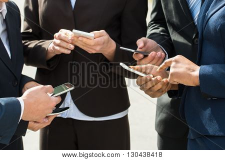 Close-up Of Businesspeople Using Mobile Phones In Hands