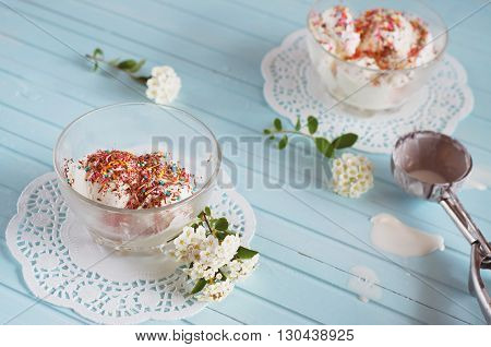 Vanilla ice cream in bowls sprinkled with chocolate and multicolored sprinkles