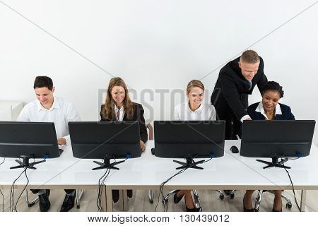 Young Businessman Helping His Colleagues In The Work Of Office