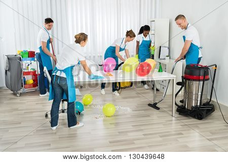 Group Of Male And Female Janitors Cleaning The Office After Party