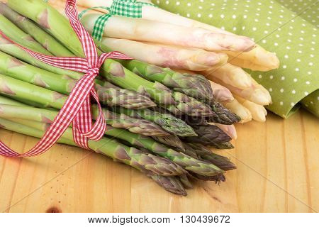 Green and white asparagus on wooden table in closeup. Vegan food vegetarian and healthy cooking concept.