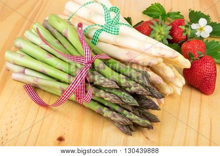 Green white asparagus with fresh strawberries on bright wood. Vegan food vegetarian and healthy cooking concept.