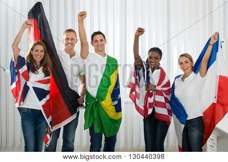 Group Of Happy Friends With Flags From Different Nations