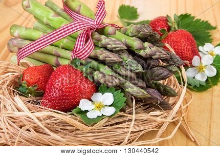 Green asparagus with strawberry in a straw nest. Retro still life.
