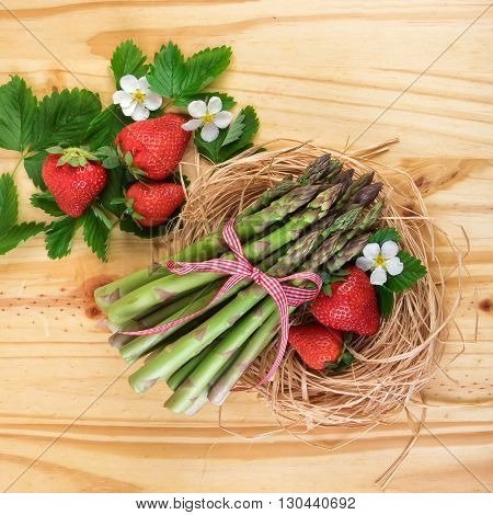 Green asparagus with strawberries. Healthy vegetables over bright wood. Top view.