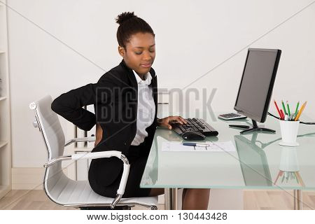 Young African Businesswoman Suffering From Backache While Working In Office