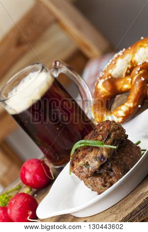 bavarian meatballs with pretzel and beer on a table