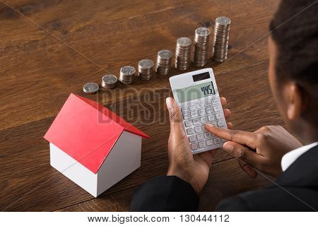Close-up Of Businesswoman Using Calculator With House Model And Stack Of Coins On Wooden Desk