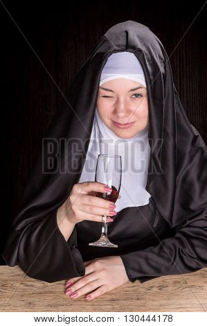 Nun sitting at a wooden table and holding wine in a glass cup and winking with one eye