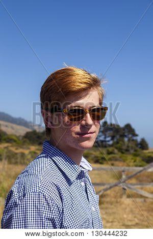 Cool Teenage Boy With Sunglasses Walks Happy On The Meadow