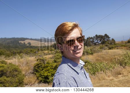 Cool Teenage Boy With Sunglasses Walks Happy On The Meadow