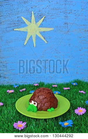 Summer food theme includes a turtle cupcake artificial grass and flowers plus the sky and sun drawn on a chalkboard.