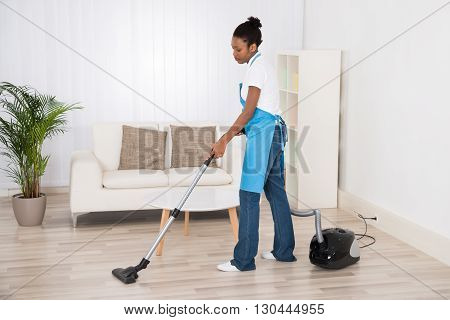 Young Female Janitor Cleaning Floor With Vacuum Cleaner In Room