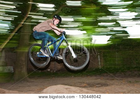 child has fun jumping with the bike over a ramp in open area