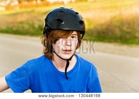 young boy is biking and wearing a helmet he takes a short rest