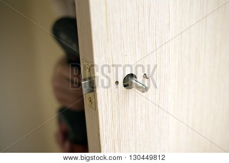 Installation of door lock using a screwdriver to. Carpenter at lock installation with electric drill into wood door.