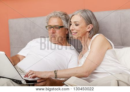Mature Couple Relaxing In Bed Reading And Chatting