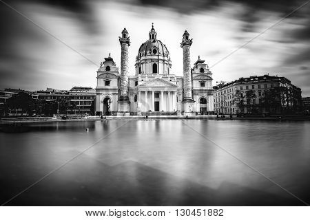 View on st. Charles's church on Karlsplatz in Vienna. White and black image with long exposure technic with blurred clouds and glossy water.