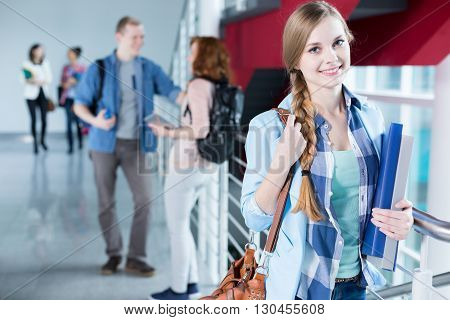 Happy female student standing in school lobby
