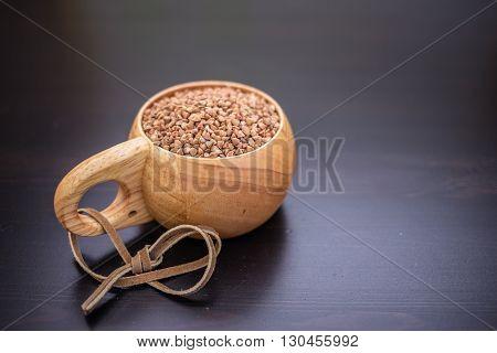 buckwheat groats in the wooden mug on black table