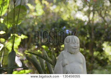 Laughing Asian male statue in botanical garden Spring Hill, Florida.