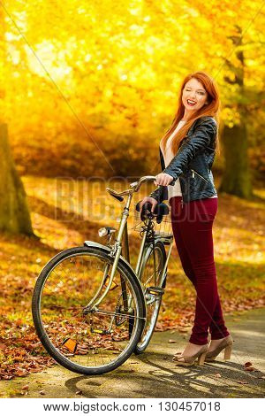 Fall active lifestyle concept. Beauty young redhaired woman fashion girl relaxing in autumn park with bicycle outdoor