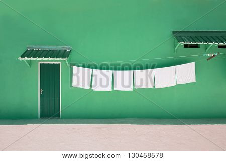 clothesline with white towels front of green wall with green door