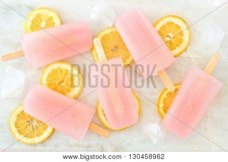 Group Of Pink Lemonade Popsicles With Lemon Slices, Ice Cubes On A White Marble Background
