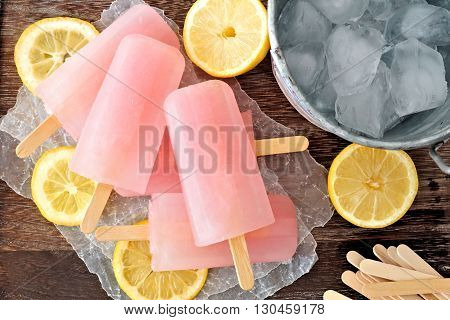 Pink Lemonade Popsicles With Ice Pail And Lemon Slices On A Rustic Wood Background