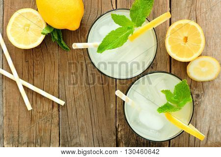 Two Glasses Of Lemonade With Straws And Mint, Overhead View On Rustic Wooden Background