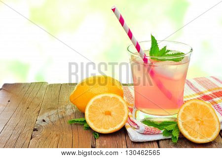 Glass Of Cold Pink Lemonade With Lemon Slices And Mint, On Wood With Outdoors Background