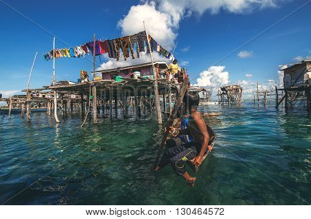 Denawan Island Sabah Malaysia - April 30 2016 : A shot of a group of children in a wooden boat paddling close to their homes. The houses here were built on stilts over shallow water.