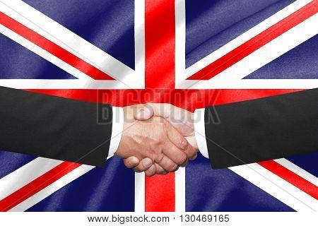 two businessmen shakehand over uinted kingdoml flag