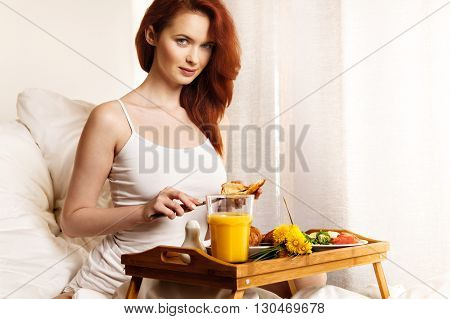 Young Woman Eats Breakfast In Bed In The Morning.