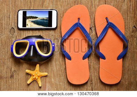 high-angle shot of a rustic wooden table full of summer stuff, such a pair of flip-flops, a diving mask, a starfish and a smartphone with the picture of a beach taken by myself in its screen
