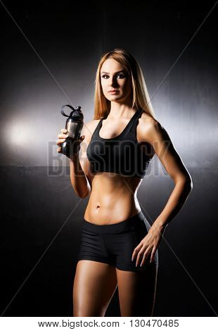 Fit, healthy and sporty woman in sportswear. Sporty girl drinks water.