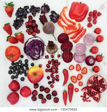 Healthy red and purple super food of fresh fruit and vegetables over distressed white background. High in antioxidants, vitamins, anthocyanins and dietary fiber.