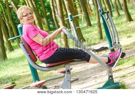 Elderly senior woman in sports wear exercising upper and lower body on outdoor gym in sunny park trainer machine healthy sporty lifestyles and slimming concept