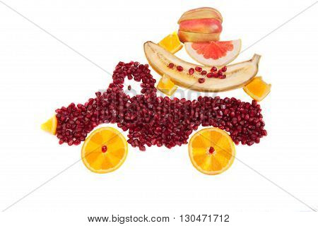 Seeds of pomegranate and slices of orange are as shape of lorry with cargo from apple orange banana and grapefruit
